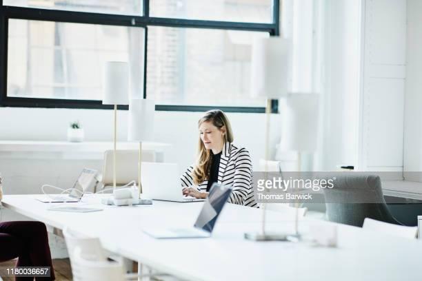businesswoman working on laptop in coworking office - independência imagens e fotografias de stock