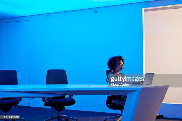 businesswoman working on laptop in meeting room at night - images photos et images de collection