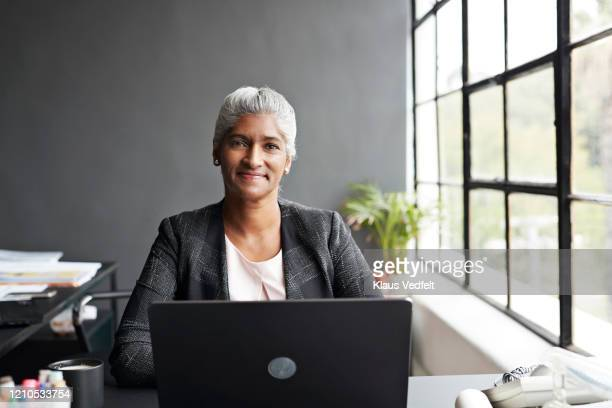 businesswoman working on laptop in modern office - business person stock pictures, royalty-free photos & images