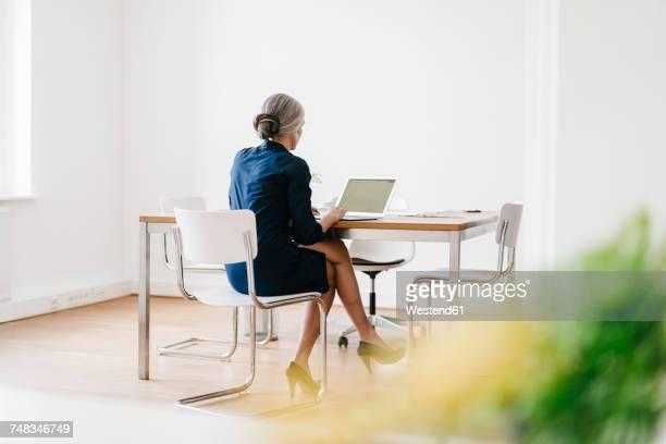 businesswoman working on laptop in office - weibliche führungskraft stock-fotos und bilder