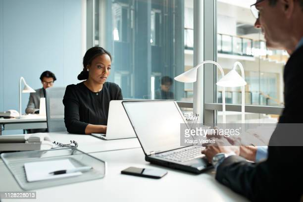 businesswoman working on laptop in open office - flexplekken stockfoto's en -beelden