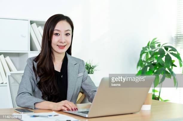 businesswoman working on laptop in the office - gray jacket stock pictures, royalty-free photos & images
