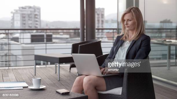 businesswoman working on laptop - gray blazer stock pictures, royalty-free photos & images