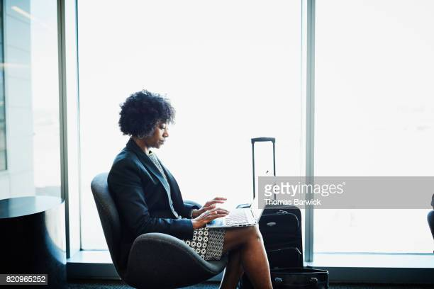 Businesswoman working on laptop while waiting for flight in airport
