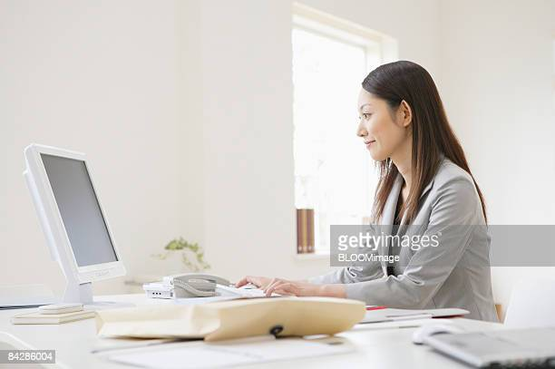 Businesswoman working on PC, side view