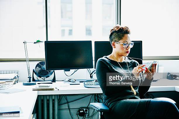 Businesswoman working on smartphone in office