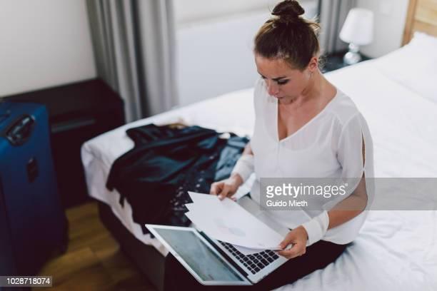 Businesswoman working online in hotelroom.