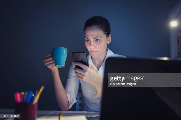 Businesswoman working overtime late at night at the laptop. She is using a mobile phone