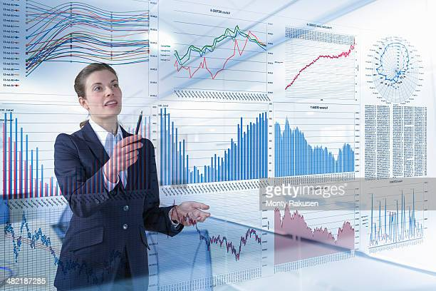 Businesswoman working with graphs and charts seen through screen