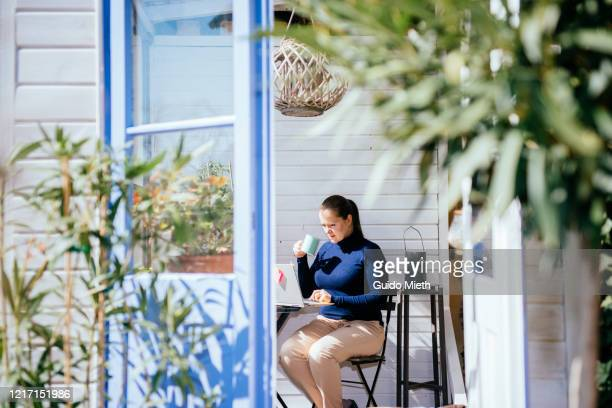 businesswoman working with laptop in green house. - guido mieth stock pictures, royalty-free photos & images