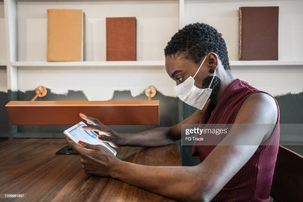 Businesswoman working with mask using digital tablet at work : Stock Photo
