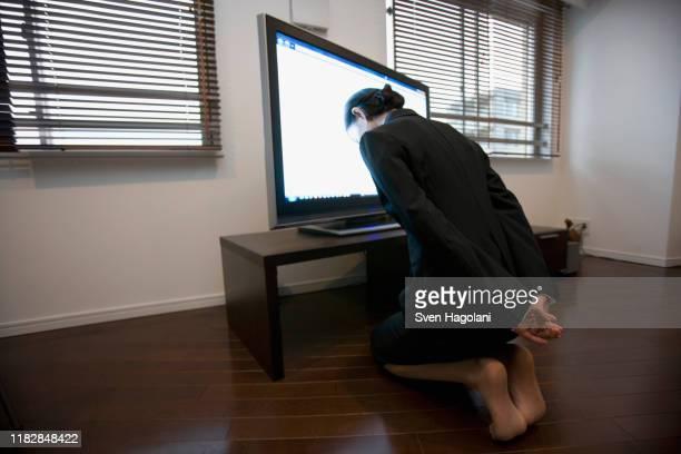 a businesswoman worshipping a television - mulher orando de joelhos imagens e fotografias de stock