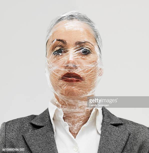 Businesswoman wrapped in plastic wrap, close-up, portrait