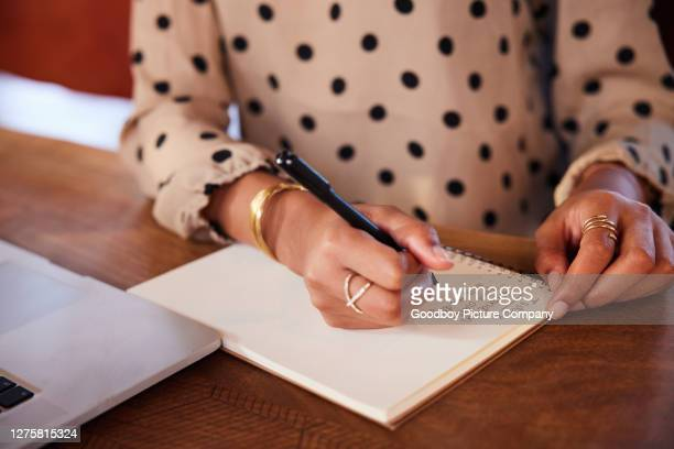 businesswoman writing a to do list while working at a table - to do list stock pictures, royalty-free photos & images