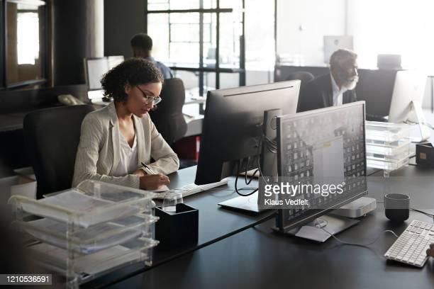 businesswoman writing at modern desk in office - abbigliamento da lavoro formale foto e immagini stock
