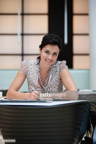 Geschäftsfrau Schreiben auf Schreibtisch