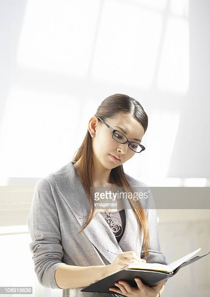 Businesswoman writing down in a notebook