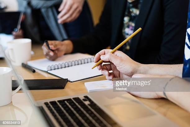 Businesswoman writing during meeting at office