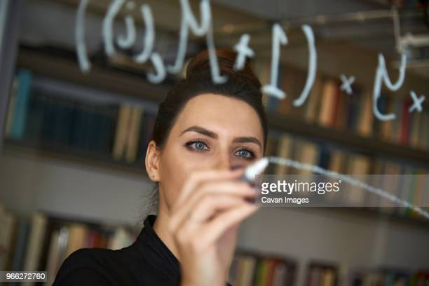 businesswoman writing formula on glass wall at office - ganar dinero fotografías e imágenes de stock