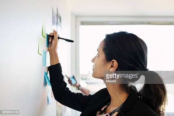 Businesswoman writing in adhesive note on wall in office