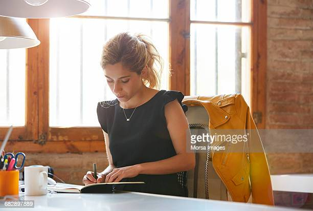 businesswoman writing in book at desk - writing stock pictures, royalty-free photos & images