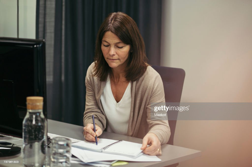 Businesswoman writing in diary while sitting at desk in office : Stock Photo