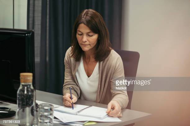 Businesswoman writing in diary while sitting at desk in office