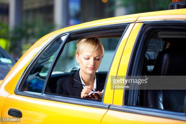 Businesswoman writing notes in yellow cab taxi