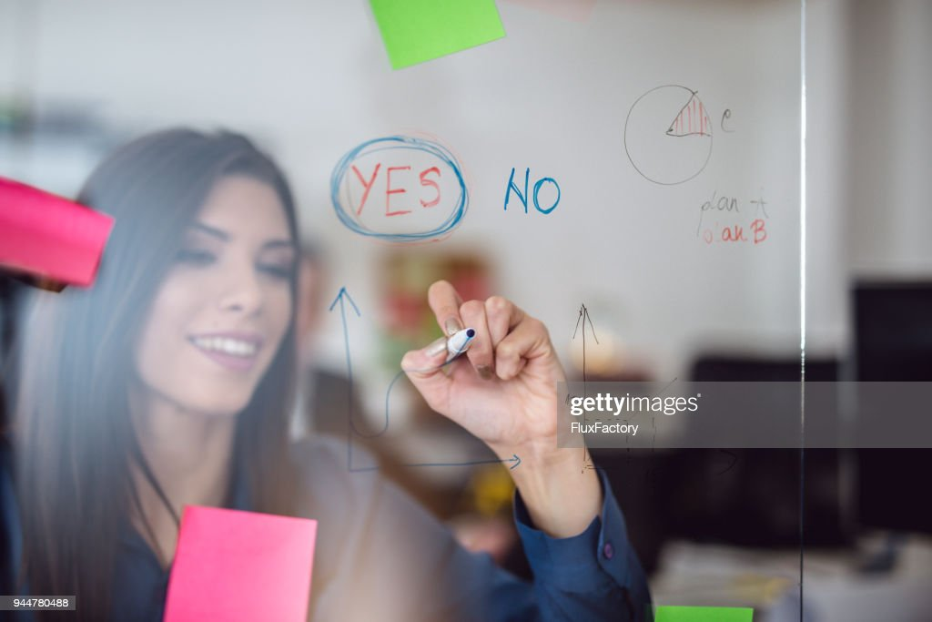Businesswoman writing on a glass board : Stock Photo