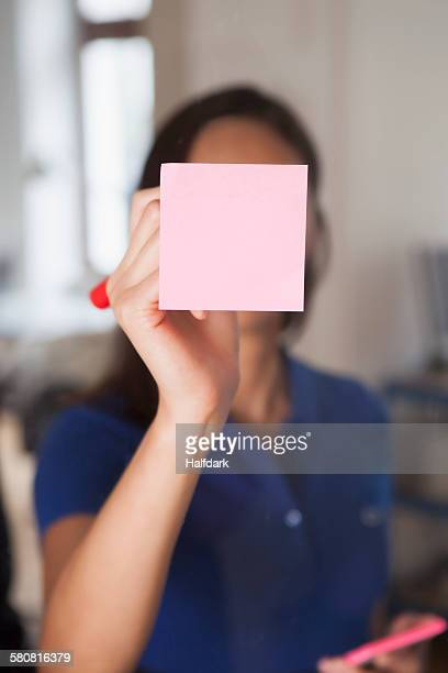Businesswoman writing on adhesive note stuck on glass wall