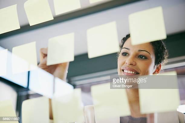 businesswoman writing on adhesive notes - oliver eltinger stock-fotos und bilder