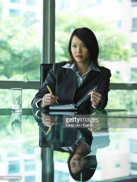 Businesswoman Writing On Book At Glass Desk In Office