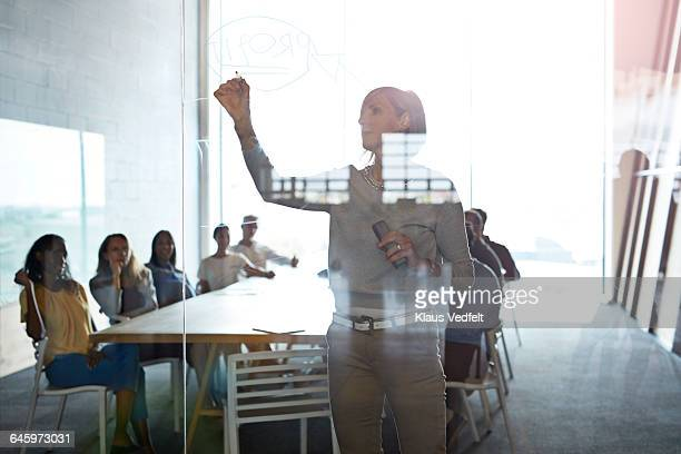 Businesswoman writing on glasswall at presentation