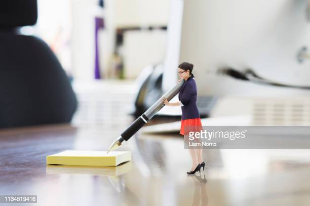 businesswoman writing on large adhesive label on oversized desk - manufactured object stock pictures, royalty-free photos & images