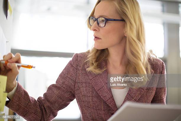 Businesswoman writing on note