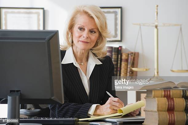 businesswoman writing on notepad - legal defense stock pictures, royalty-free photos & images