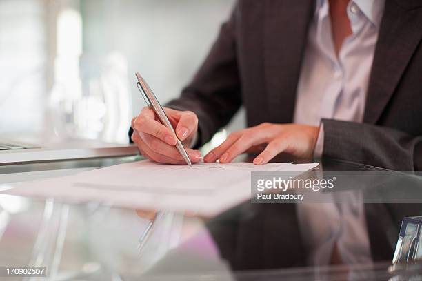 Businesswoman writing on paper at desk
