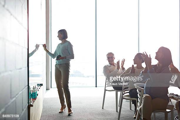 Businesswoman writing on whiteboard at meeting