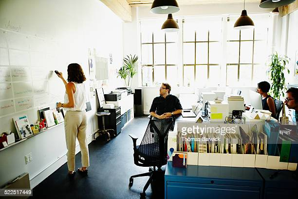 businesswoman writing on whiteboard in office - leanintogether stock pictures, royalty-free photos & images