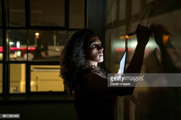 Businesswoman writing on whiteboard over tablet computer in dark office