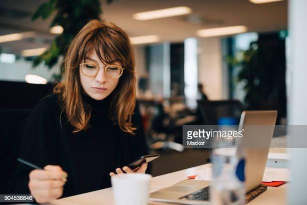 businesswoman writing while holding mobile phone at desk in office - freelancer stockfoto's en -beelden
