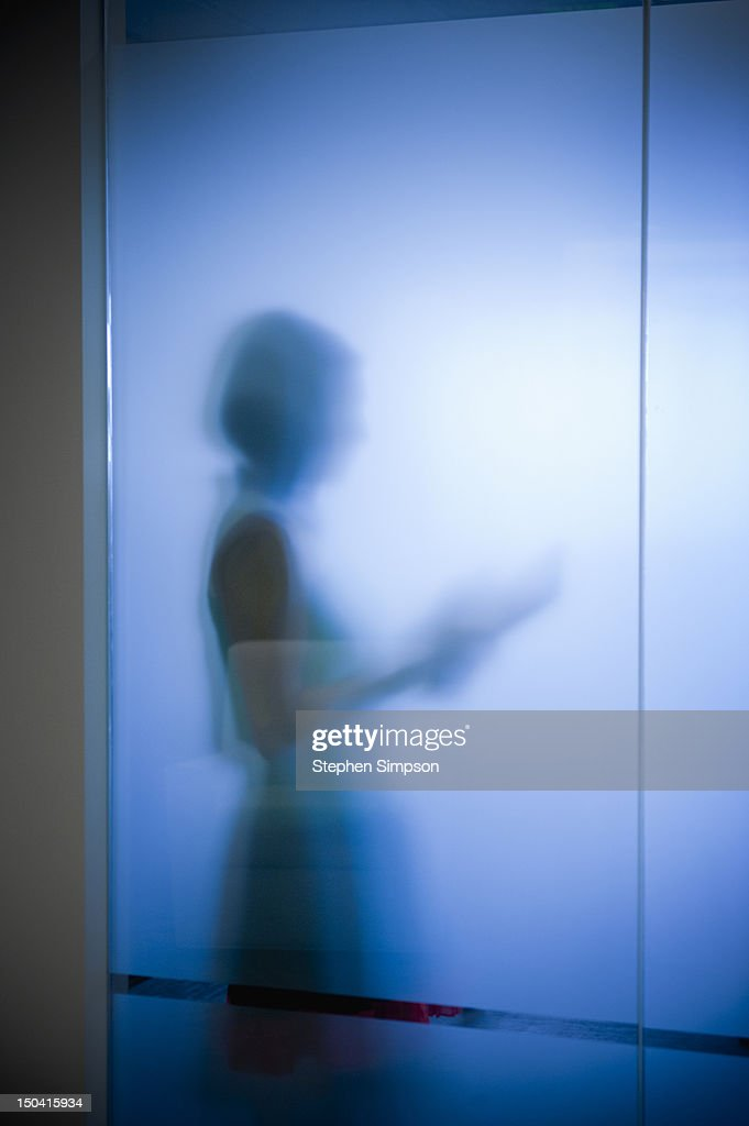 businesswoman w/tablet computer, frosted glass : Stock Photo