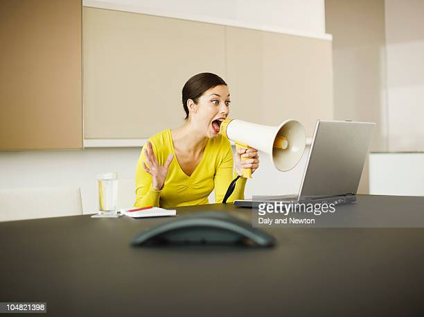 Businesswoman yelling at laptop with bullhorn in conference room