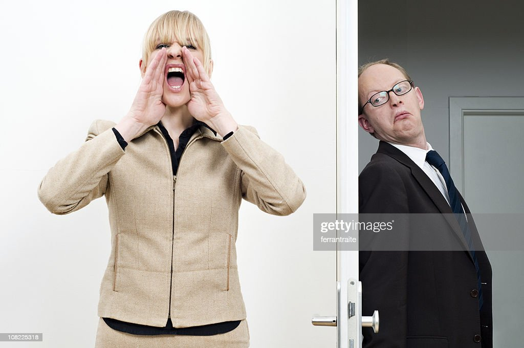 Businesswoman Yelling For Hiding Businessman : Stock Photo