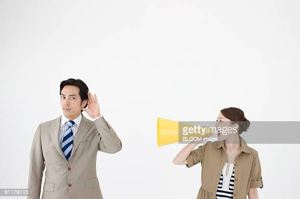 Businesswoman yelling into megaphone at businessman
