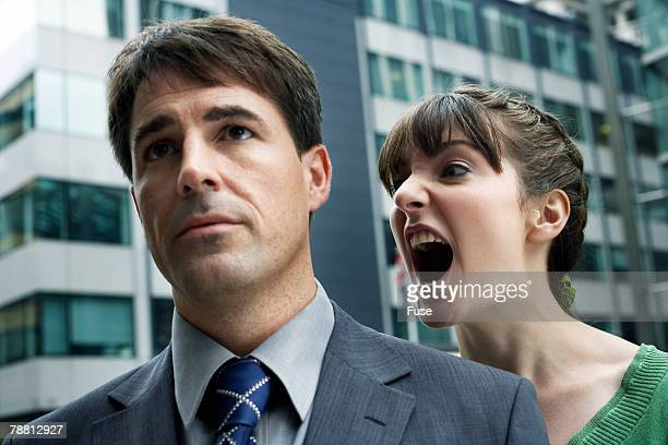 Businesswoman Yelling Loudly into Another's Ear