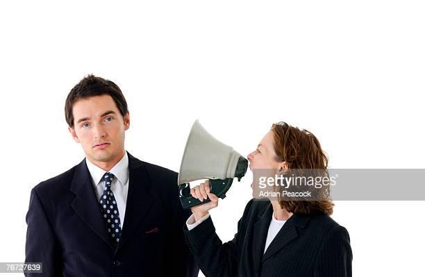 Businesswoman yelling through megaphone at businessman