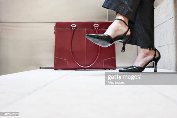 businesswomans feet in high heeled shoes and her purse. - leather purse stock pictures, royalty-free photos & images