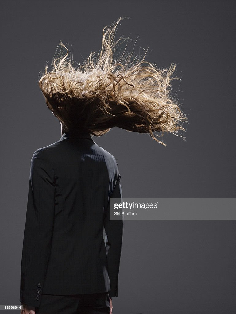 Businesswoman's hair blowing in wind : Stock Photo