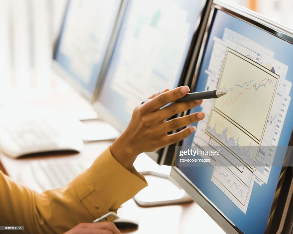 Businesswoman's hand with stylus points to monitor : Stock Photo